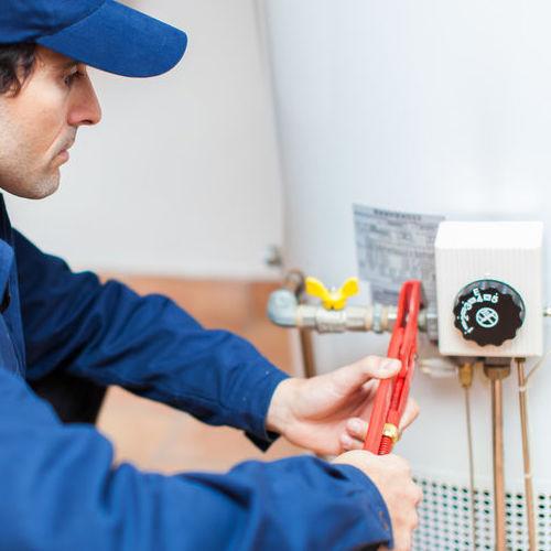 A Technician Adjusts a Water Heater.