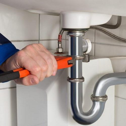 Hands Using an Orange Wrench to Fix a Bathroom Pipe.