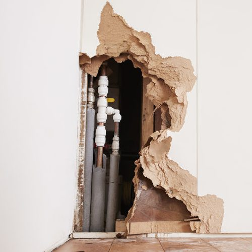 A Damaged Wall Exposing a Burst Water Pipe.