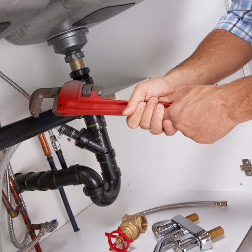 Hands Holding a Red Wrench Under a Kitchen Sink.