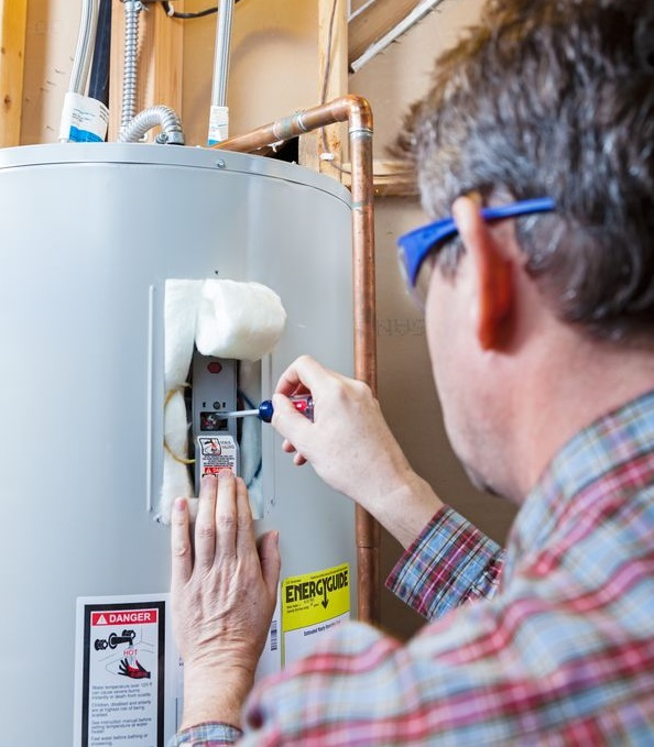 A Man Doing a Repair On a Water Heater.