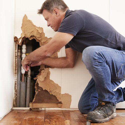 A Man Repairing a Burst Water Pipe.