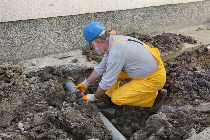 A Plumber Fixing a Sewer Pipe.