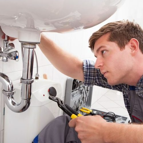 A Plumber Fixing a Sink in a Bathroom.