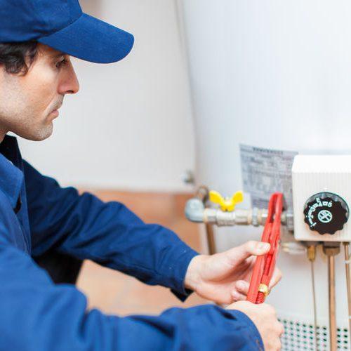 A Plumber Repairing a Water Heater.