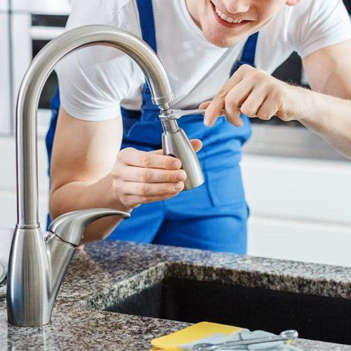 A Plumber Repairing a Kitchen Faucet.
