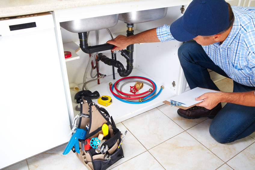 A Plumber with Tools in a Kitchen.